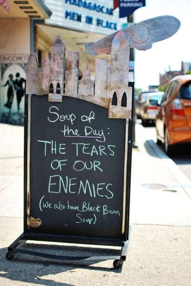 A-frame sign on sidewalk written in chalk